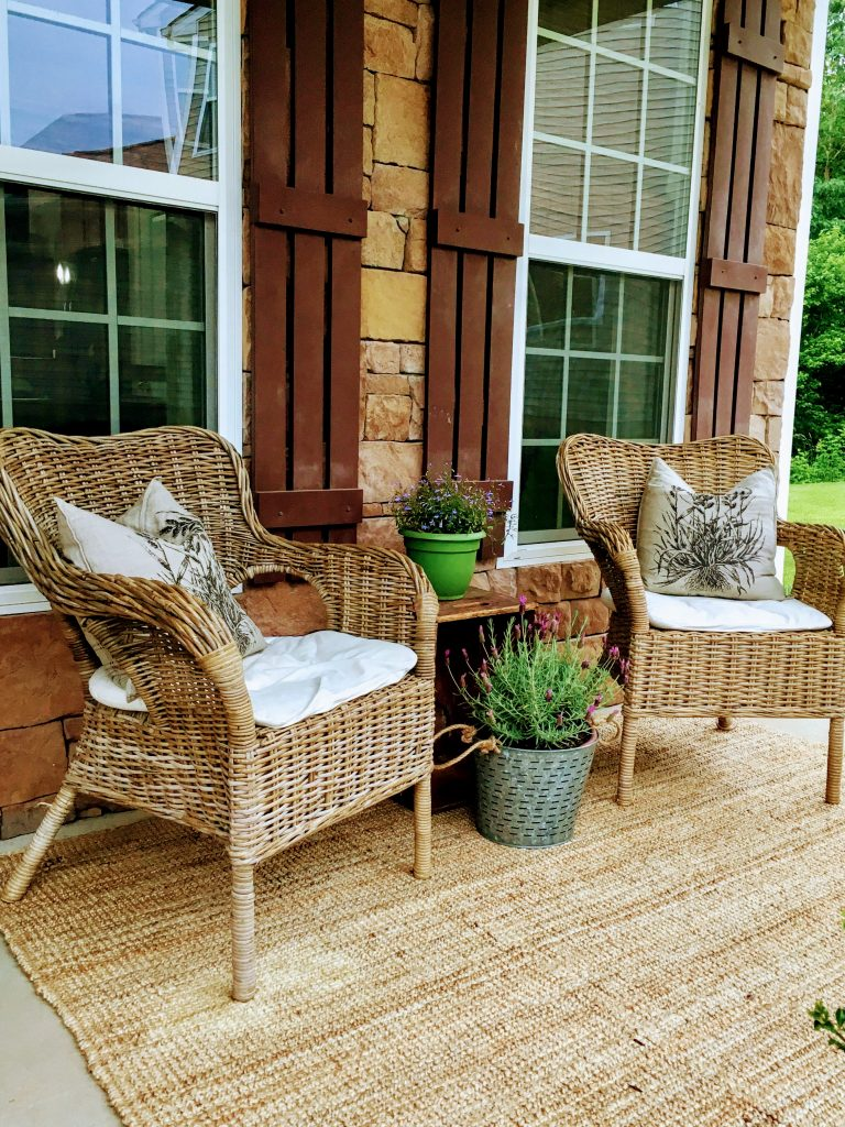 twp wicker chairs on front porch with potted flowers