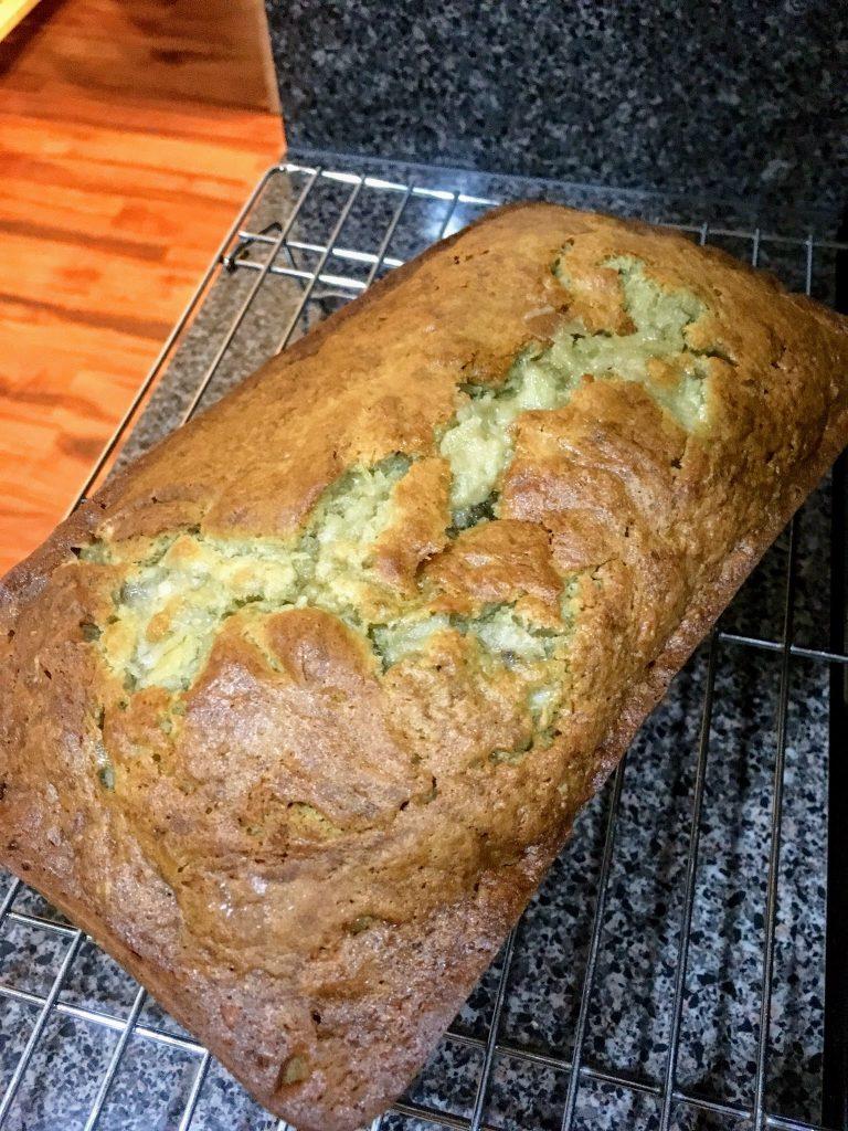 big loaf of banana bread cooling on rack