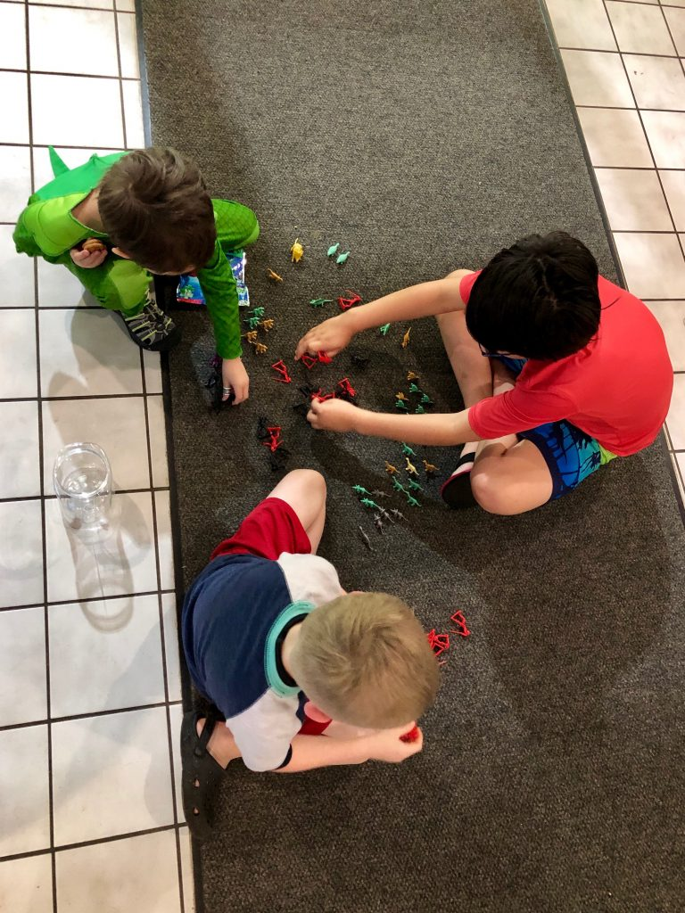 three little kids playing with legos on the floor