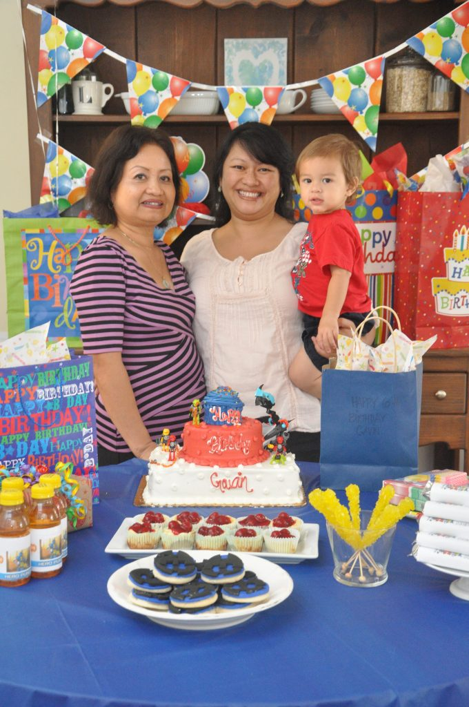 two ladies and a baby in front of birthday cake