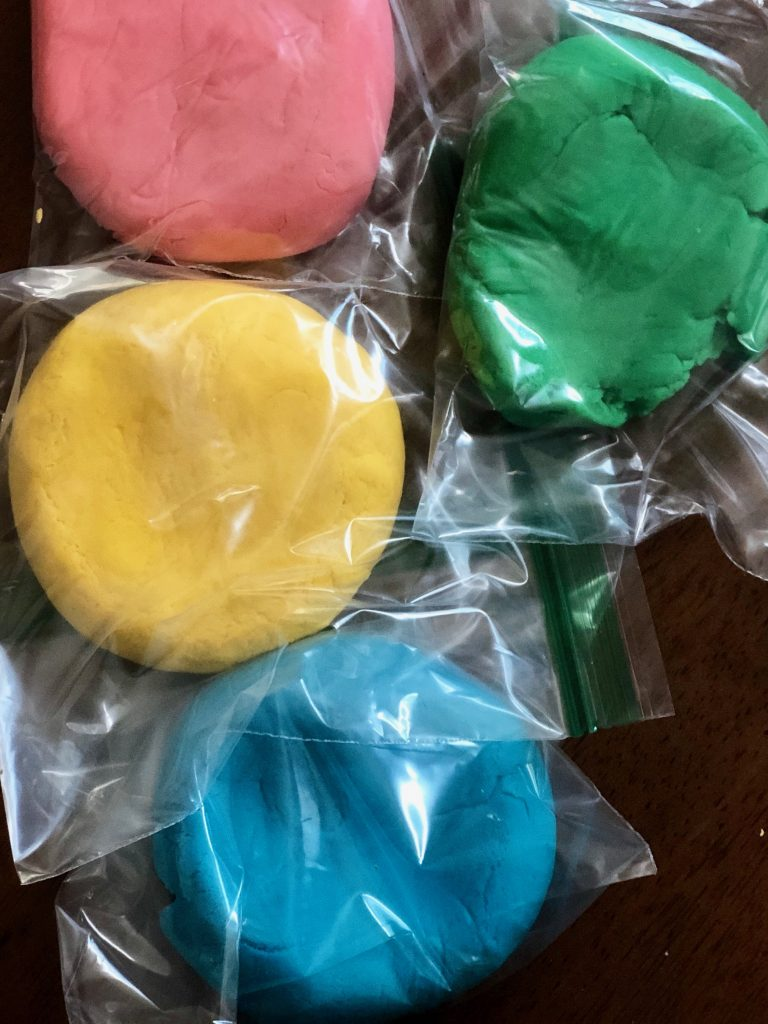 pink red yellow and green play dough in plastic bags