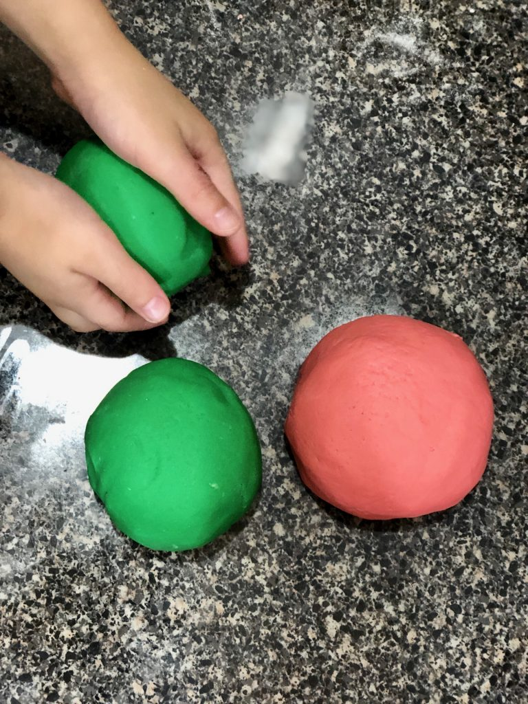 Little hand playing with green and pink play dough