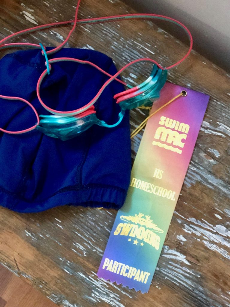 blue swim cap with googles and a swimming ribbon