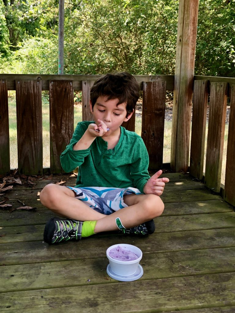 little boy in green shirt enjoying blueberry ice cream